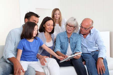 3-generación familia sentado en el sofá con tablet electrónica