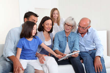 3-generation family sitting in couch with electronic tablet Stock Photo - 9903310