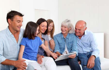 adultos: 3-generaci�n familia sentado en el sof� con tablet electr�nica