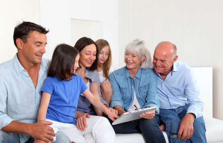 3-generation family sitting in couch with electronic tablet photo