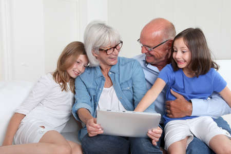 grandkids: Senior people with grandkids using electronic tablet