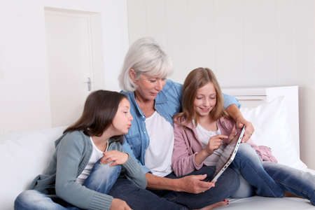 Senior woman with grandkids playing with touchpad photo