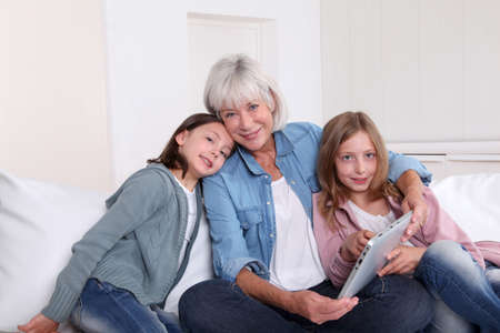 grandkids: Senior woman with grandkids playing with touchpad Stock Photo