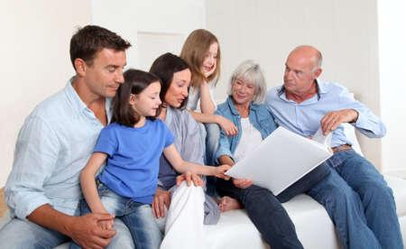 3-generation family looking at photo album photo
