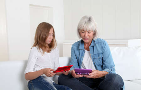 Senior woman and girl playing with gaming console photo