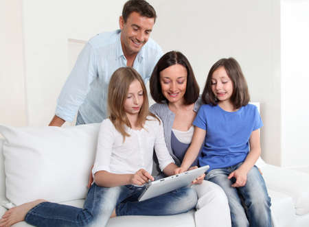 Parents and children using electronic tablet at home Stock Photo - 9903062