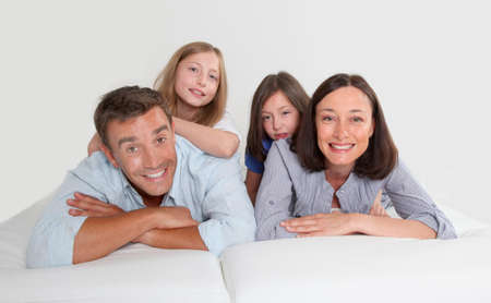 Family of 4 people laying down couch photo