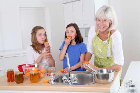 Senior woman making apricot jam with grandkids Stock Photo - 9907126