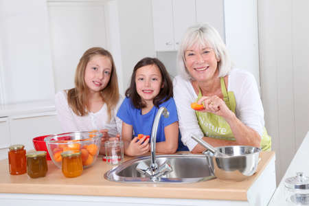 grandkids: Senior woman making apricot jam with grandkids