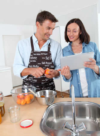 Couple cooking fruit jam at home photo