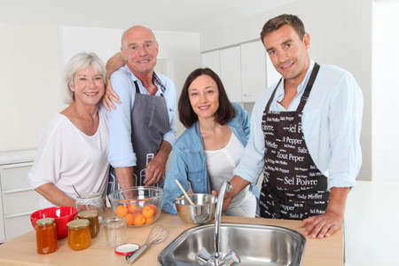 Family preparing fruit jam in home kitchen photo