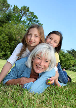 grandkids: Senior woman lying down in park with girls on his back