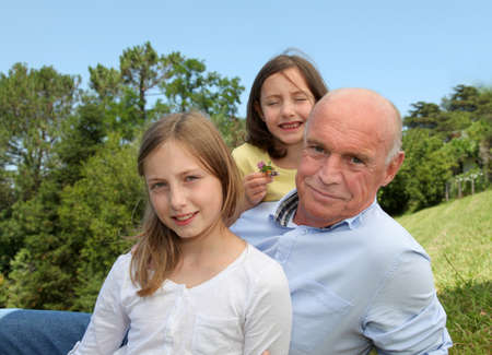 grandkids: Grandfather with grandkids sitting in park