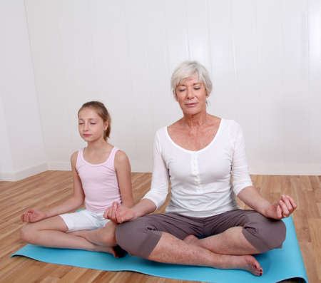 Senior woman with young girl doing yoga exercises photo