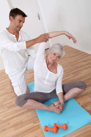 physiotherapist: Sport coach training senior woman with stretching exercises