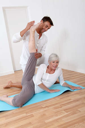 Sport coach training senior woman with stretching exercises photo