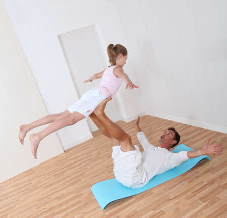gymnastics girl: Man holding young girl with feet Stock Photo