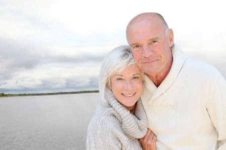 mature couple: Portrait of happy senior couple standing by a lake Stock Photo