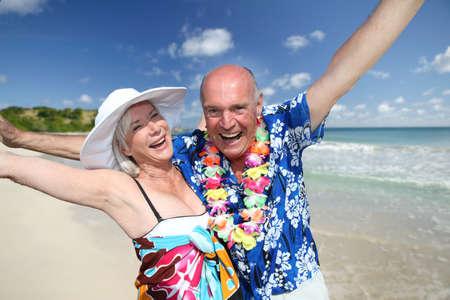 Happy senior couple at tropical beach photo