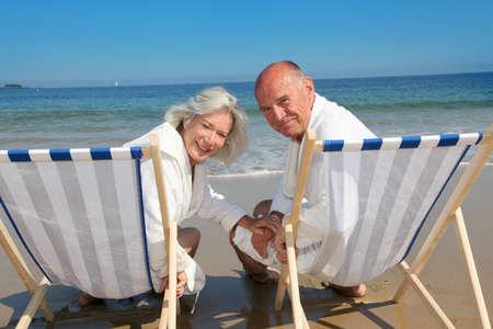 jubilados: Retrato de pareja senior sentados en tumbonas
