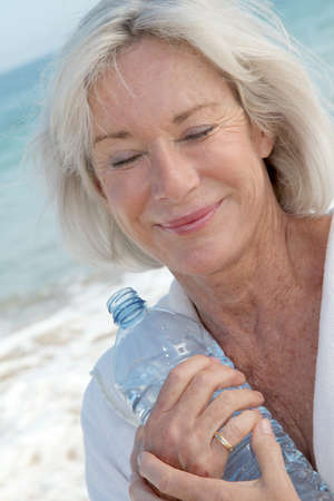 Senior woman drinking water from bottle photo