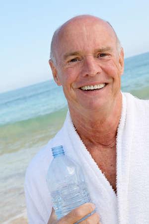 bathrobe: Portrait of smiling senior man with bottle of water
