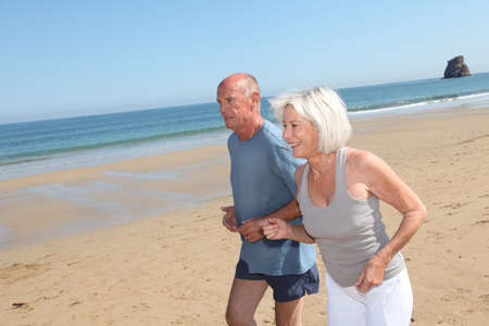 Senior couple jogging on a sandy beach photo