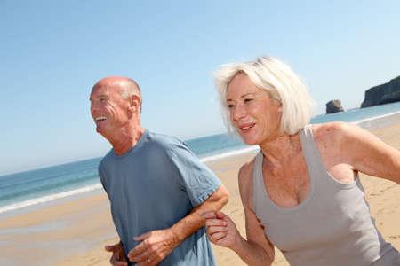 breathing exercise: Senior couple jogging on a sandy beach Stock Photo