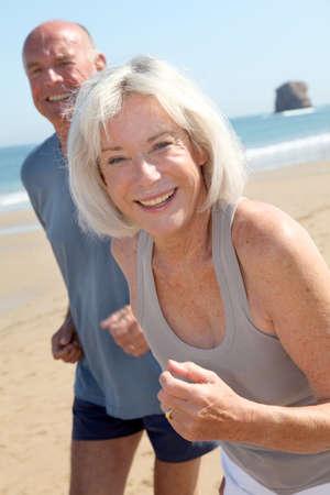 personas trotando: Matrimonios de edad para correr en una playa de arena Foto de archivo