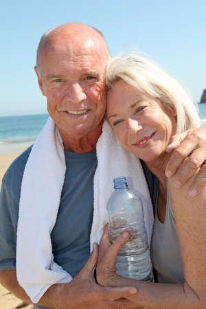 Portrait of athletic senior couple on the beach photo