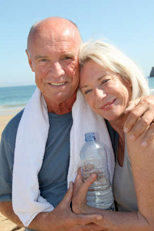 Portrait of athletic senior couple on the beach photo