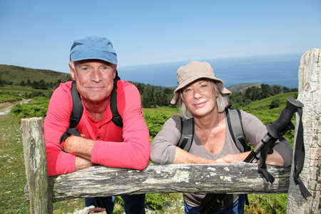 Senior hikers standing by a fence Stock Photo - 9903405