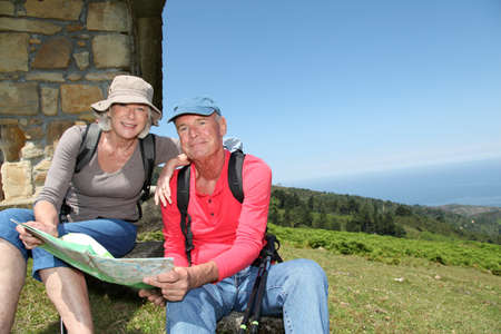 Senior couple looking at map on hiking day photo