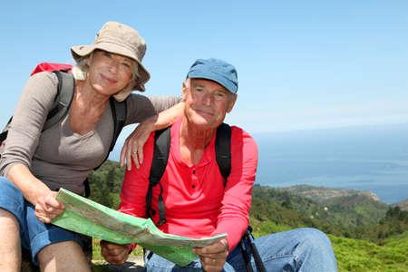 rambling: Senior couple looking at map on hiking day
