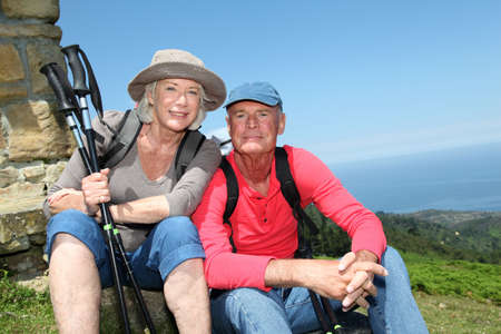 Portrait of happy senior hikers resting by stone house Stock Photo - 9903400