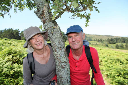 Portrait of happy senior couple hiking in natural landscape photo
