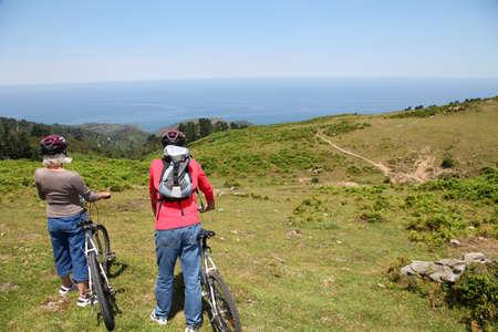 andando en bicicleta: Senior pareja mirando un paisaje durante el paseo en bicicleta