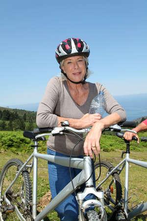 Portrait of happy senior woman on mountain bike photo