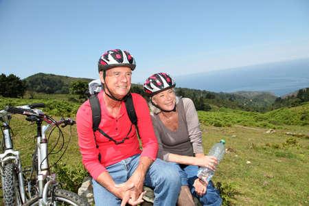 tercera edad: Matrimonios de edad andar en bicicleta de monta�a en paisaje natural