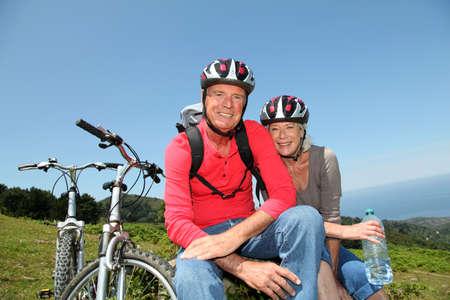 Senior couple riding mountain bikes in natural landscape photo