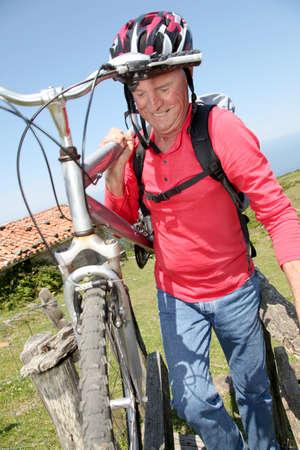Senior man carrying mountain bike photo