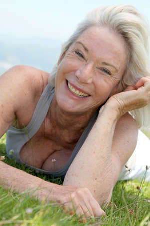 Portrait of cheerful senior woman in natural landscape photo