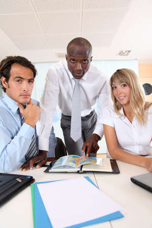 Office workers sitting around meeting table photo