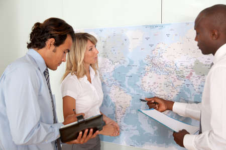 Business team looking at world map photo