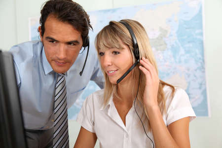 telephone saleswoman: Woman and sales manager in office with headset on Stock Photo