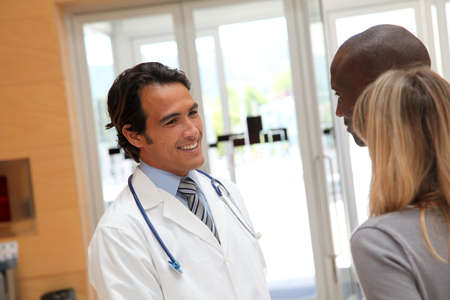 appointment: Doctor talking to couple in hospital hall Stock Photo