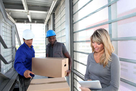 managing: Businesswoman in warehouse controlling goods reception Stock Photo