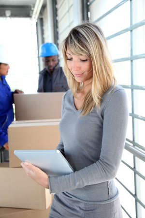 Businesswoman in warehouse using electronic tablet photo