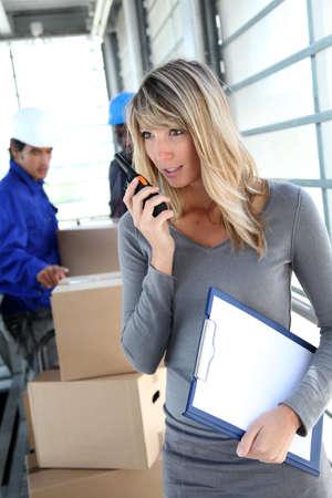 Businesswoman in warehouse using walkie-talkie photo