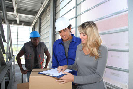 Manager with storemen controlling goods delivery Stock Photo - 9909192
